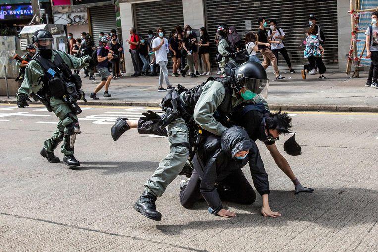 De Hongkongse politie greep zondag hard in met traangas, waterkanonnen en pepperspray. Beeld AFP