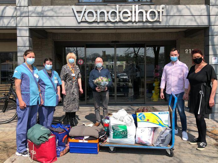 Verzorgend personeel van WZC Vondelhof,  directrice Reinhilde Dierick, Guido Vandevelde nemen de kledij van Ingrid en Lenny in ontvangst die ze samen met de Boutersemse Feestvrienden inzamelden.