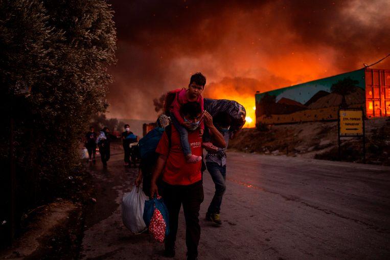 Inwoners van het kamp Moria op het Griekse eiland Lesbos vluchten voor de vlammen.  Beeld AFP