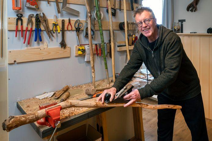 Henk Cornelissen (71) maakt een wandelstok van een tak uit het bos.