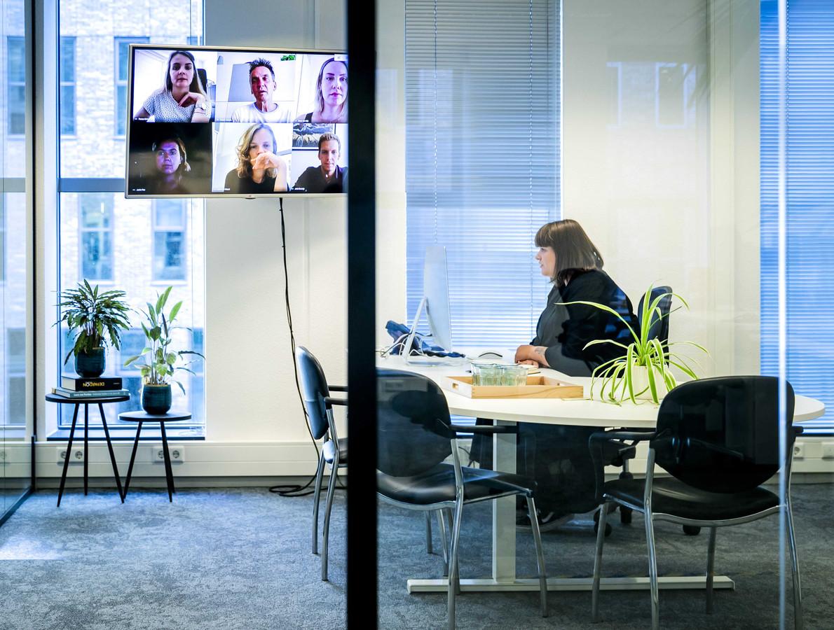 Een werknemer tijdens een videogesprek op kantoor eerder dit jaar. Haar collega's werken vanuit huis.