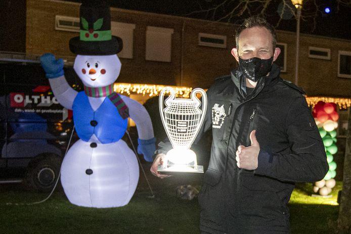 Emiel Willemsen met de bokaal die zijn carnavalsvereniging De Sökkestoppers uitreikt voor de mooist verlichte straat van Heino.