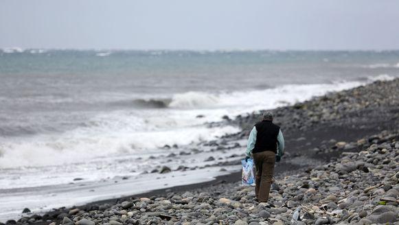 Een Maleisische expert zoekt naar brokstukken van Malaysia Airlines-vlucht MH370 op een strand van het eiland La Réunion.