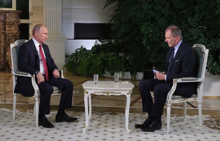 Vladimir Poetin in gesprek met de Oostenrijkse journalist Armin Wolf. Wellicht had hij de kritische toon niet verwacht. Beeld EPA