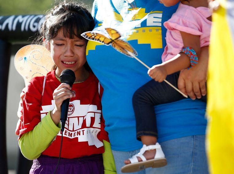 De 8-jarige Akemi Vargas vertelt op een protestbijeenkomst hoe zij werd gescheiden van haar vader. Het meisje is inmiddels weer met haar familie herenigd.  Beeld AP