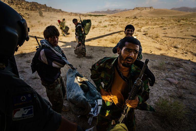 Afghaanse soldaten slepen hun bezittingen mee naar een legerhelikopter. Ze kunnen steeds minder op luchtsteun rekenen. Beeld Getty Images