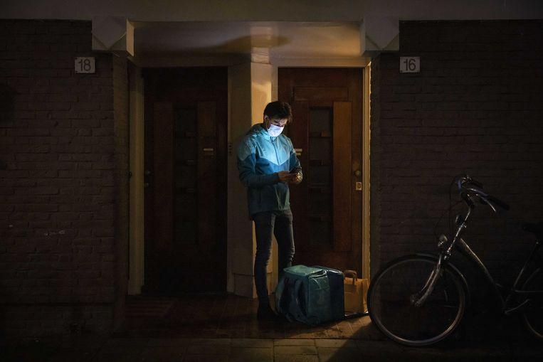 Een bezorger van Deliveroo aan het werk. Eten kan tijdens de avondklok nog besteld worden.  Beeld ANP