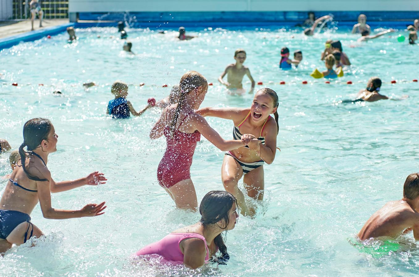 Kinderen zoeken verkoeling in zwembad 't Kuipje te Heesch.