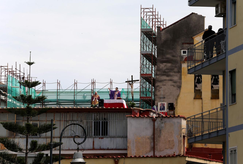 Vanaf hun balkon volgen Italianen in Napels een mis in de open lucht, opgediend door twee priesters van de parochie Santa Maria della Salute.