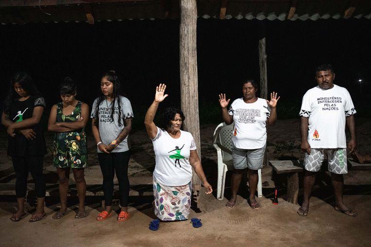 Dorpshoofd Myy'Paw (55) knielt neer tijdens het gebed op zondagavond. Myy'Paw behoorde in Monte Alegre tot de weigeraars van het vaccin.  Beeld Ian Cheibub