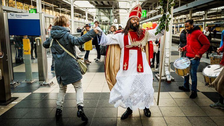 De Nieuwe Sint maakt samen met een brassband een feest op het perron van het Amstelstation. Beeld anp