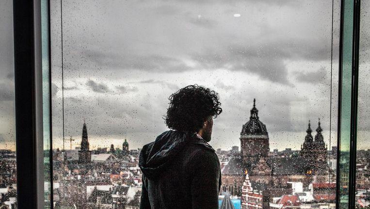 Aziz kijkt uit over Amsterdam waar hij woont en werkt. Beeld null