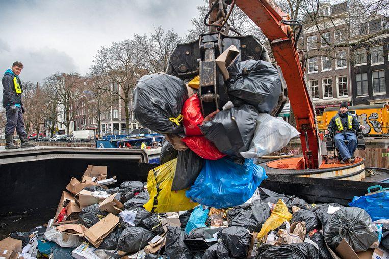 Vuilnismannen van de gemeente storten met kleine vrachtwagens het afval van de stad in een vuilnisboot op de Kloveniersburgwal. Beeld Guus Dubbelman / de Volkskrant