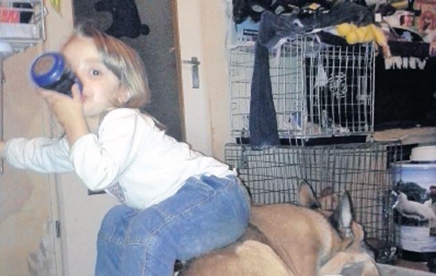 De 2-jarige Amika zittend op de rug van herdershond Luna. De peuter is door Jeugdzorg uit huis geplaatst.