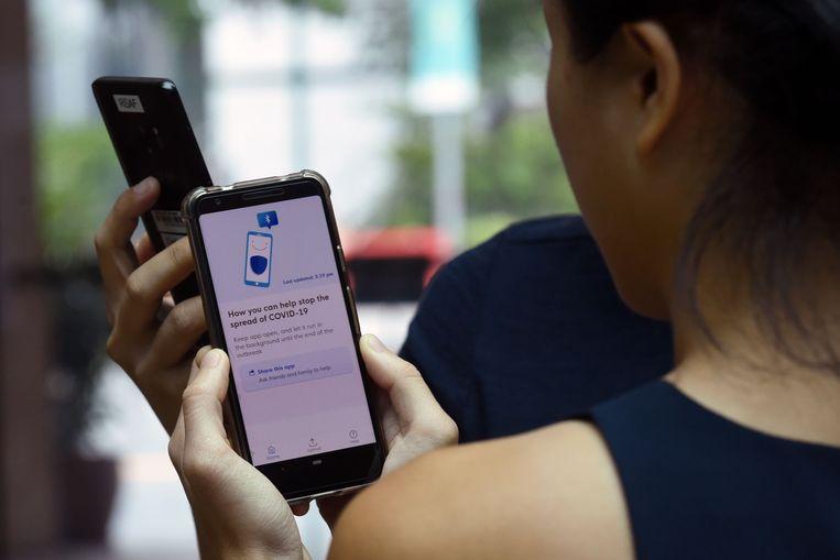 In Singapore is een app gelanceerd waarop men kan zien wie contact heeft gehad met een coronapatiënt. Beeld AFP