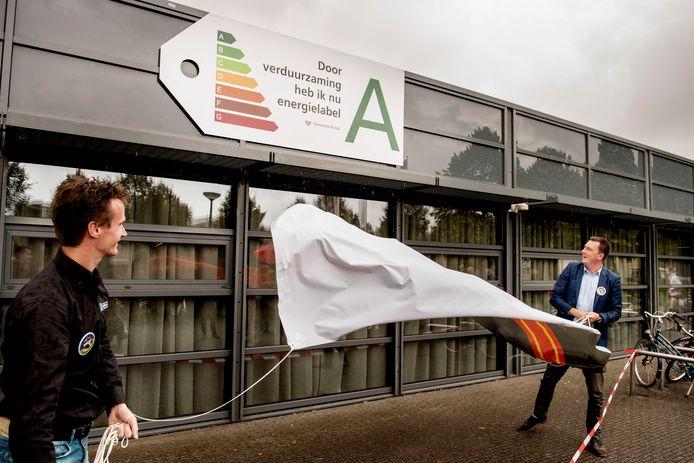 Sporthal De Drie Linden in Prinsenbeek heeft nu energielabel A gekregen. Bestuursvoorzitter Rob Hennekam (links) en wethouder Paul de Beer onthullen het bord.