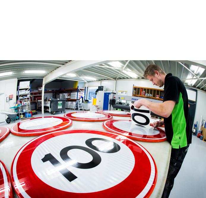 Bij Visser print & sign in Assen worden nieuwe verkeersborden voor de maximale snelheid 100 km per uur beplakt.