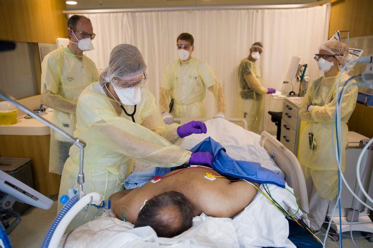 Een patiënt op de corona ic van het Rotterdams Ikazia ziekenhuis wordt verzorgd door verpleegkundigen en artsen. Beeld Arie Kievit