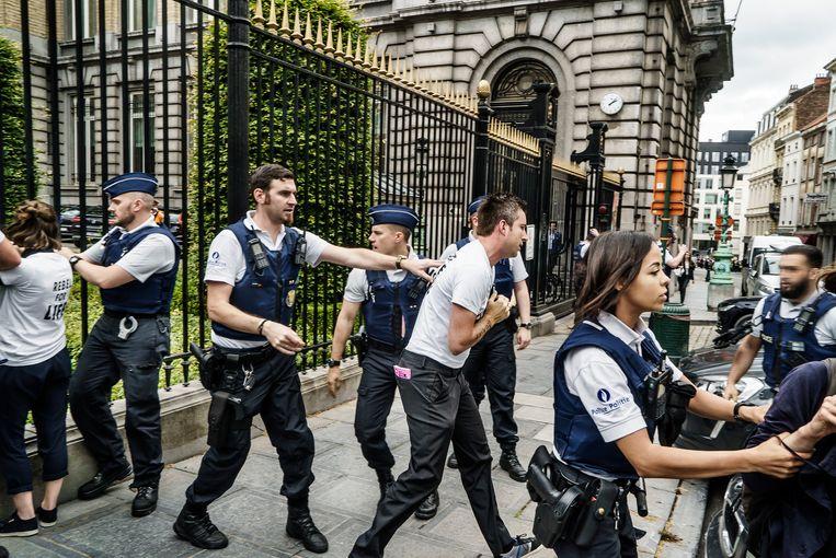 Agenten trekken de actievoerders los van het hek en sturen hen weg. Beeld Eric de Mildt