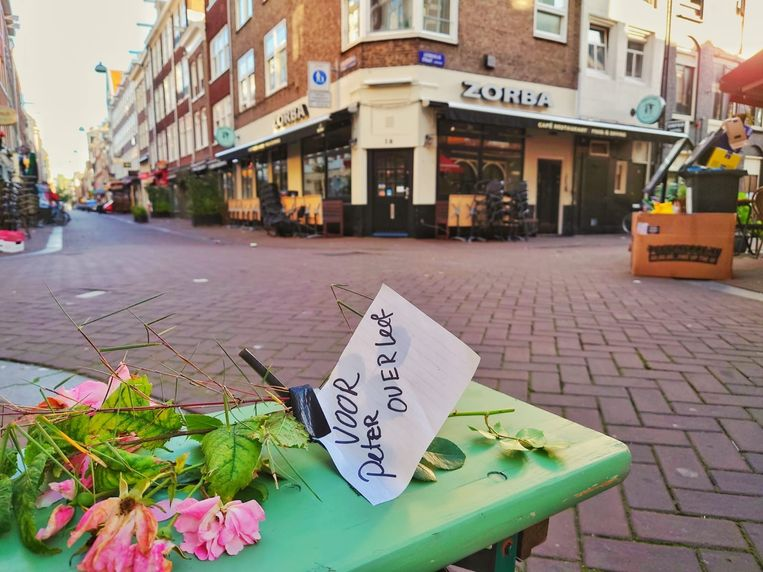 In Amsterdam zijn bij de plek waar De Vries is neergeschoten al vroeg mensen op de been. Sommigen laten bloemen of een boodschap achter. Beeld Noël van Bemmel