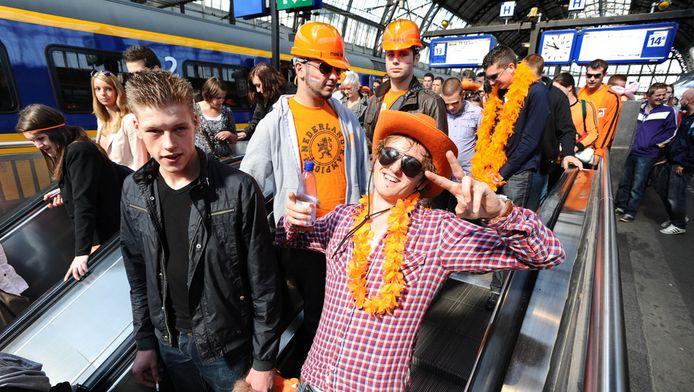 Oranje uitgedoste feestvierders komen aan op Amsterdam CS.
