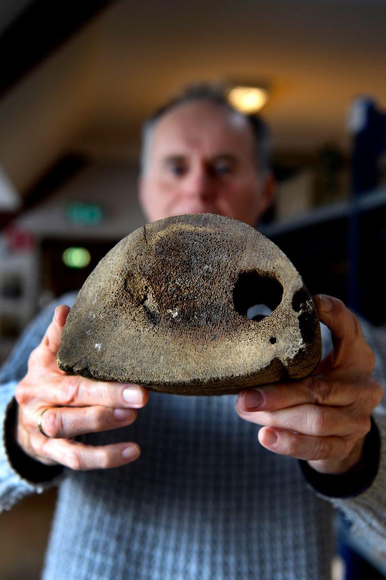 Stadsarcheoloog Piet Kleij toont een schijf van een walviskaak in het archeologisch depot in Zaandijk.  Beeld Olaf Kraak