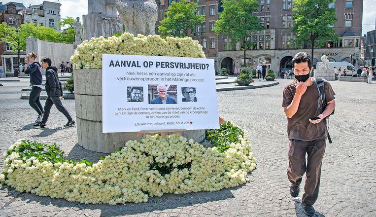 Een anonymus heeft op de Dam in Amsterdam duizenden witte rozen voor Peter R de Vries gelegd, met een poster waarin wordt betwijfeld dat de moordaanslag een aanval is op de persvrijheid.  Beeld Guus Dubbelman / de Volkskrant