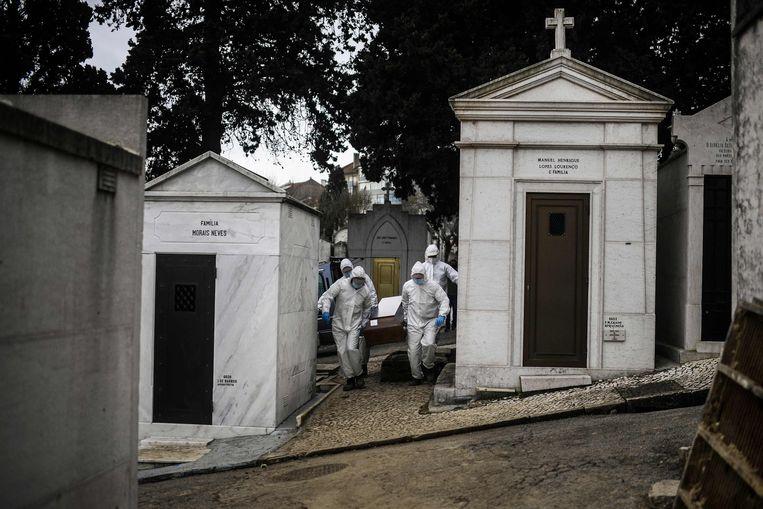 Grafdelvers in beschermende pakken aan het werk op de begraafplaats Alto de São João in Lissabon. Beeld AFP
