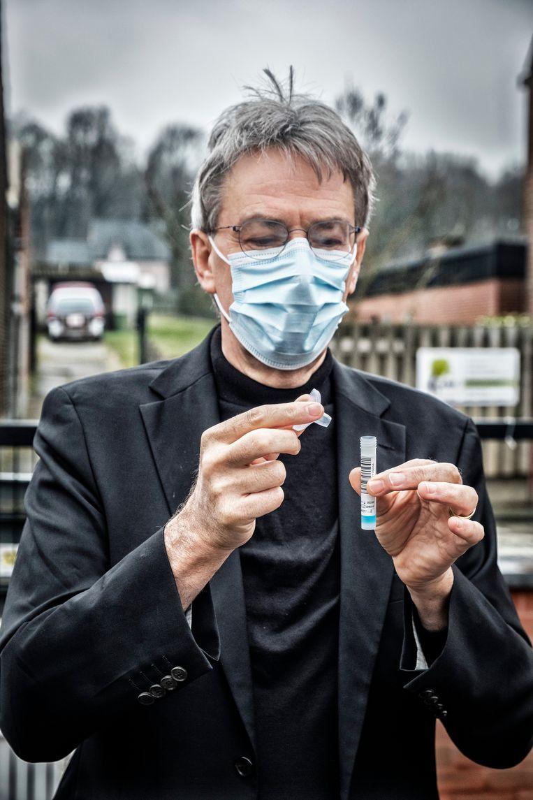 Professor microbiologie Herman Goossens demonstreert de speekseltests in een school in Diest.  Beeld Tim Dirven