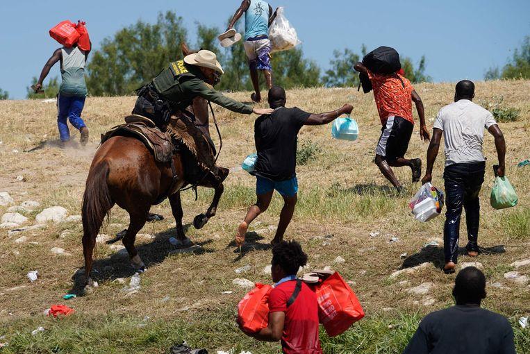 Een agent probeert een migrant tegen te houden bij de grens in Del Rio. Beeld AFP