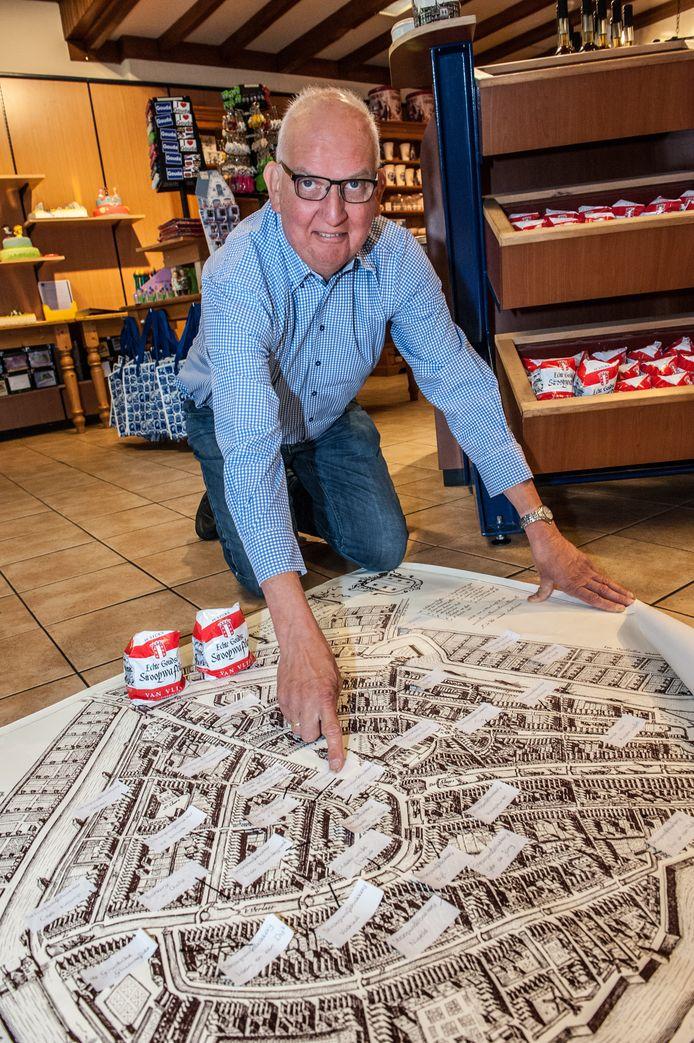 Cees van den Berg toont op een oude plattegrond van Gouda met stickers de plaatsen waar vroeger stroopwafels werden gebakken.