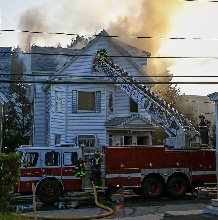 Brandweerlieden bestrijden het vuur in een huis in Lawrence. Beeld EPA