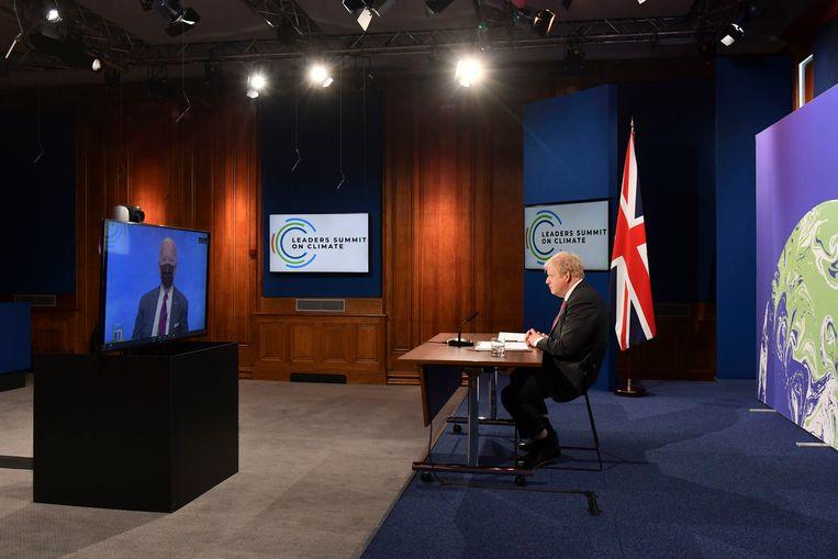 De Britse premier Boris Johnson (r) luistert tijdens een virtuele klimaattop in april naar de Amerikaanse president Joe Biden.  Beeld Justin Tallis / AP