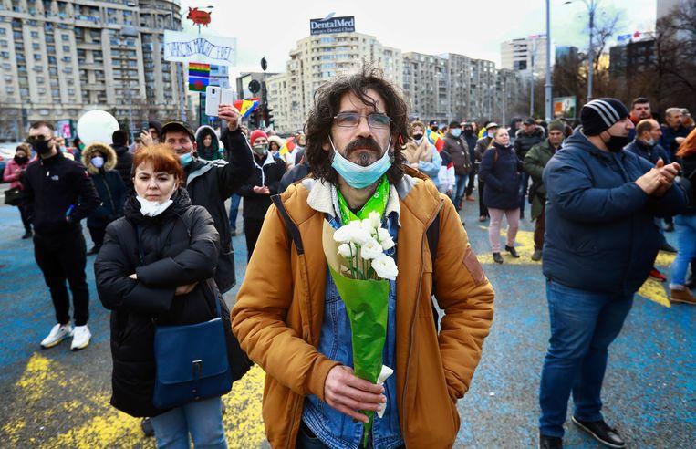 Een demonstrant in Roemenië, drie weken geleden, houdt een bos bloemen op tijdens een protestbijeenkomst tegen een nieuwe wet die vaccinaties van kinderen en volwassenen verplicht stelt.  Beeld EPA
