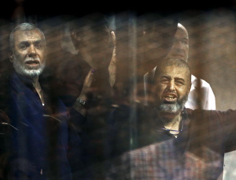 Leden van de Moslimbroederschap achter tralies horen boos een uitgesproken doodstraf aan, in een rechtbank in Caïro, Egypte.  Beeld REUTERS
