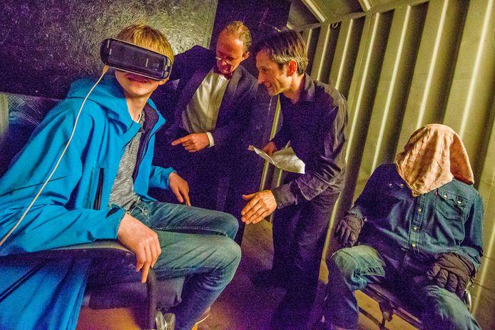 """Thijs van Dam (14, links) uit Nieuwerbrug bij het virtual reality-experiment. ,,Het was geweldig!"""" Naast hem vlnr: Dr. Crux (Ruud Boxma), Michiel van de Burgt en de 'patiënt' met doek over het hoofd."""