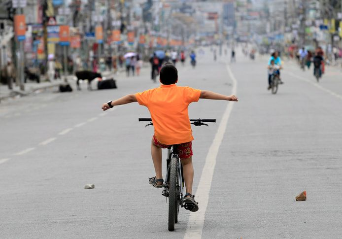 Een jongetje rijdt op zijn fiets door een lege straat in Nepal.
