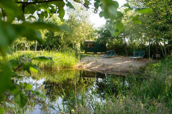 De vijver met het strandje waar normaal ook de saunawagen geplaatst wordt op de naturistencamping Grensland in Nieuwmoer.