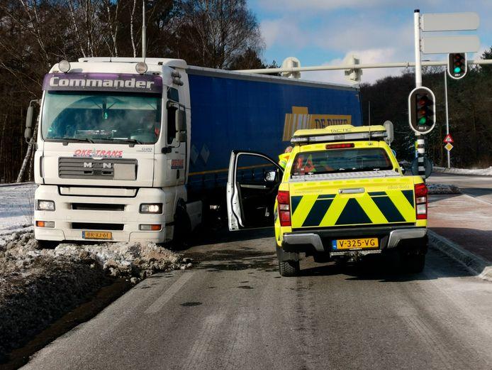 De vrachtwagen zit hopeloos vast en kan niet op eigen motor uit de blubber komen op de A12 in Ede.