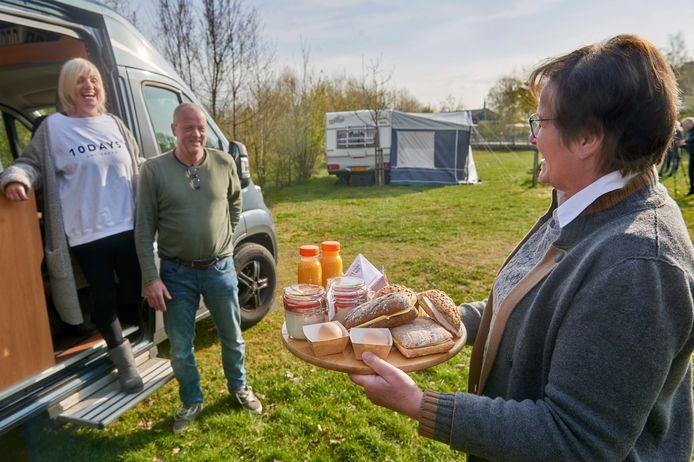 Wethouder Coby van der Pas lanceert de nieuwe website voor bezoekers en toeristen in Meierijstad. Op de foto brengt ze ontbijt bij Jaap en Astrid Mandersloot op camping Het Goeie Leven in Eerde.