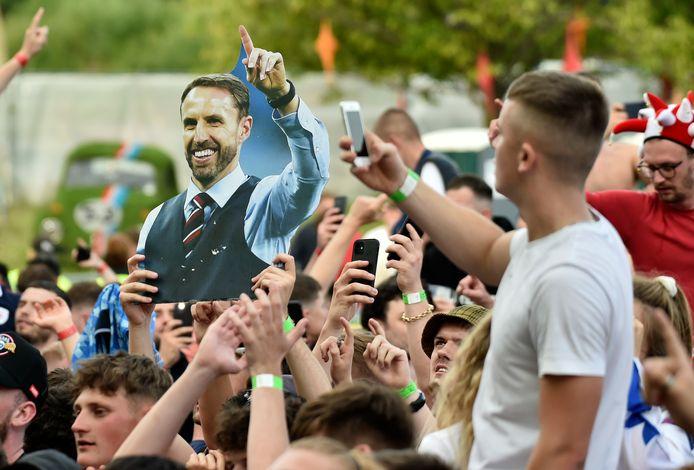 Des supporters anglais brandissent une pancarte à l'effigie du manager de l'Angleterre, Gareth Southgate, alors qu'ils célèbrent au 4TheFans Fan Park, à Manchester, en Angleterre, mardi 29 juin 2021, leur victoire au huitième de finale de l'Euro 2020 contre l'Allemagne.