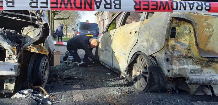 Een medewerker van forensische opsporing van politie doet onderzoek bij de auto.