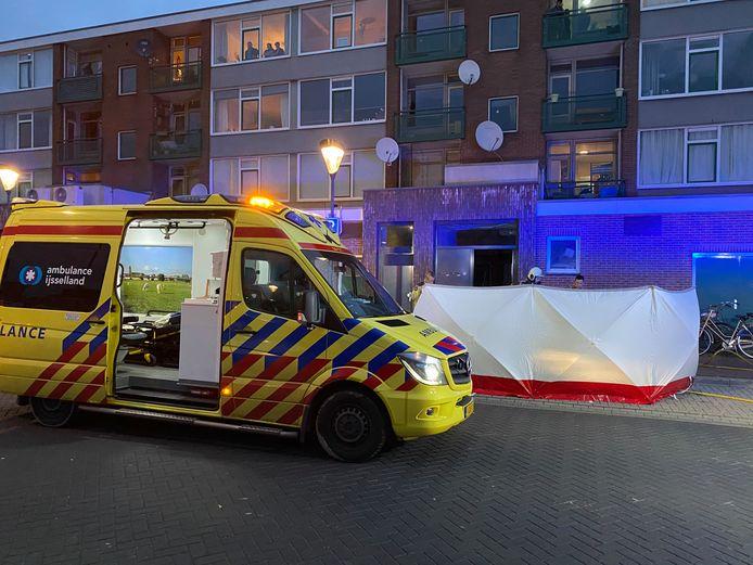 Ambulancepersoneel probeert op straat een persoon te redden die uit een brandende woning is gered.