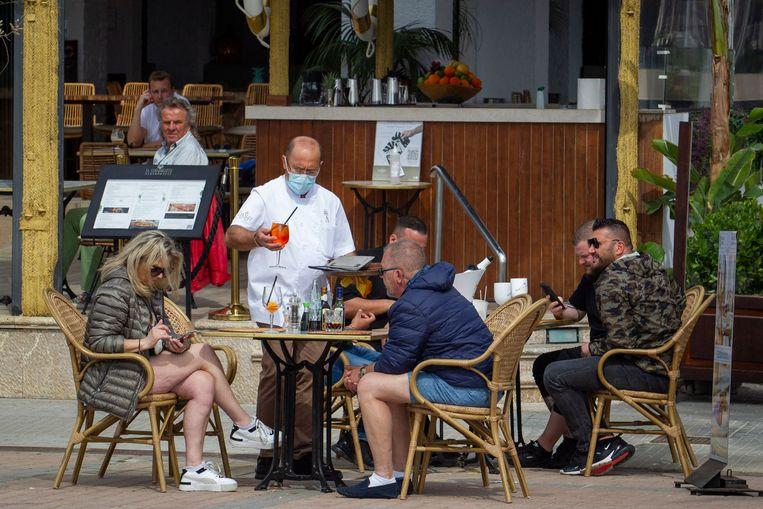 Toeristen op een terras in Palma de Mallorca.  Beeld AFP