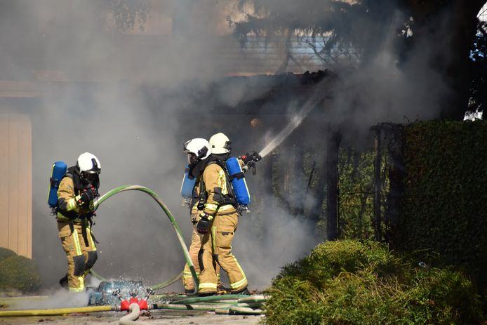De brand in de carport naast de villa langs de Ingelmunstersteenweg in Oostrozebeke woedde in alle hevigheid. Een gasfles moest worden gekoeld (zie voorgrond).