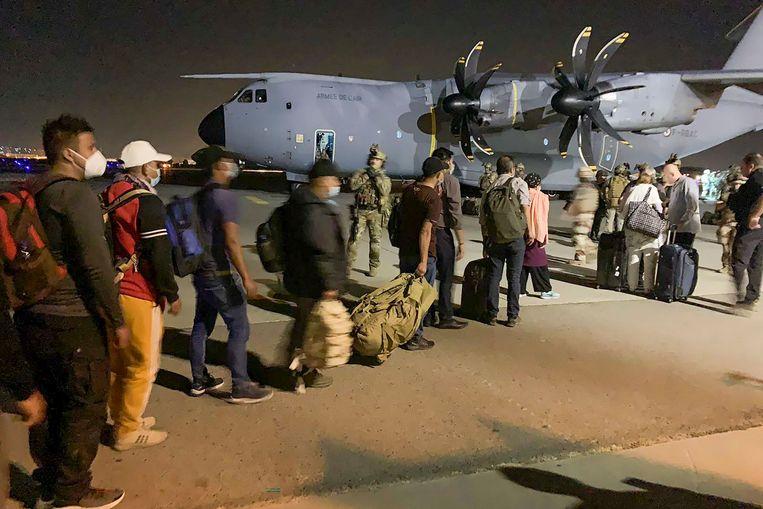 Evacués uit Afghanistan gaan aan boord van een Frans militair vliegtuig op het vliegveld van Kabul. Beeld AFP