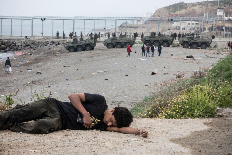 Een man rust uit na de kust te hebben bereikt. Beeld AP
