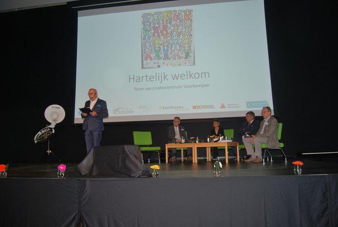Moderator dokter Jan Van Emelen op het symposium Symposium (foto 1: moderator Jan Van Emelen, foto 2: van links naar rechts Johan Van Hoof (J&J), gouverneur Cathy Berx, minister-president Jan Jambon, Wienand de Smet (hoofd departement ontwikkeling en educatie provincie Antwerpen), foto 3: Peter Missotten (huisarts)  Malle Proms (foto 4: foodtrucks, foto 5: dokter Jan Van Emelen en San Segers, foto 6: samenfeest, foto 7: samenzang)
