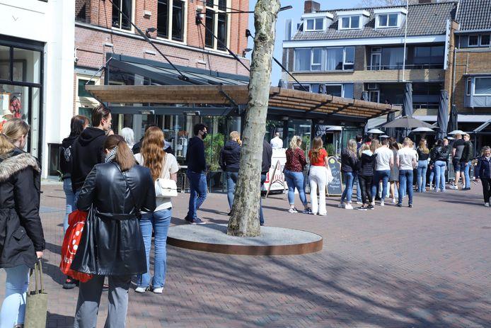 Een lange rij mensen voor Grand-Café De Twee Wezen in Hengelo.