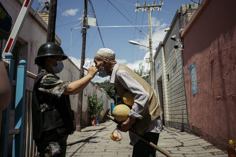 Een Oeigoerse man wordt getemperatuurd door een overheidsambtenaar in Kuqa, een stad in het westen van China. Beeld Getty